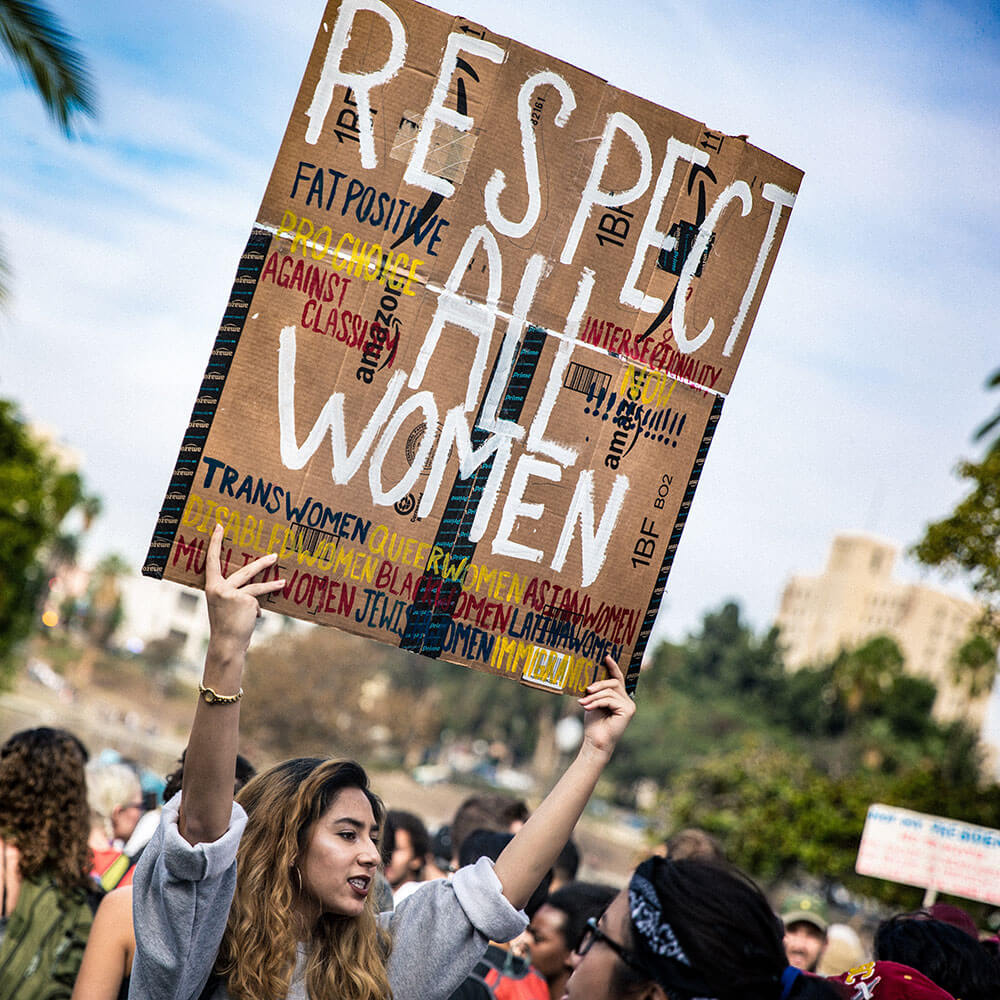 Woman holding a protest sign that says respect all women