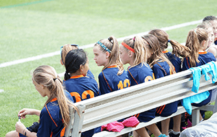 young girls at a sport game sitting on bench