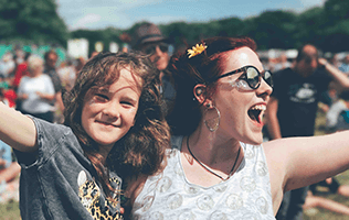 Photo of woman with a young girl smiling outside