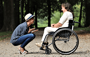 woman on wheelchair and woman squatting