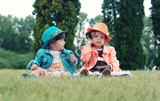 2 little girls with hats playing on the grass with microphone