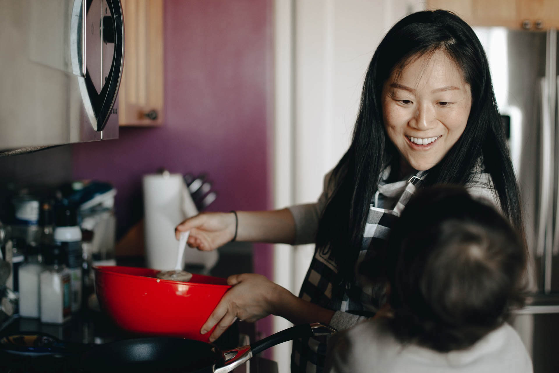 woman in kitchen performing unpaid labour.